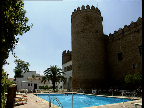stockvideo's en b-roll-footage met modern outdoor swimming pool next to castle tower a few people splashing in pool parador de zafra - buitenbad