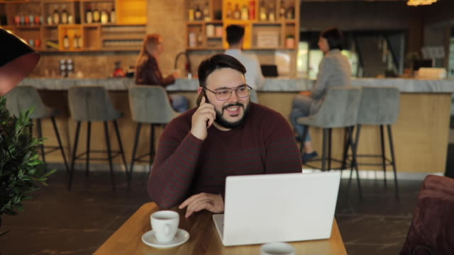 vídeos de stock e filmes b-roll de modern overweight man talking on mobile in cafe - usar portátil