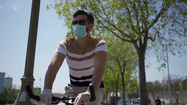 vídeos de stock e filmes b-roll de modern responsible man riding a bike on a quay near river - óculos de sol