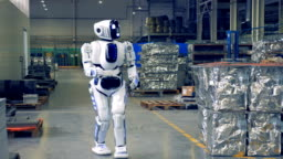 Modern robot walks in a production floor, smiling into camera.