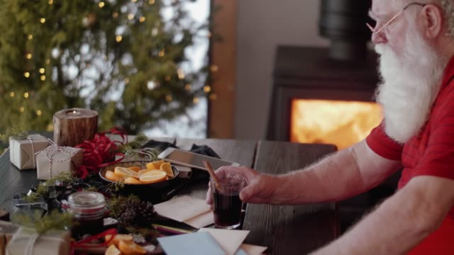 modern santa claus drinking mulled wine (slow motion) - log fire stock videos & royalty-free footage
