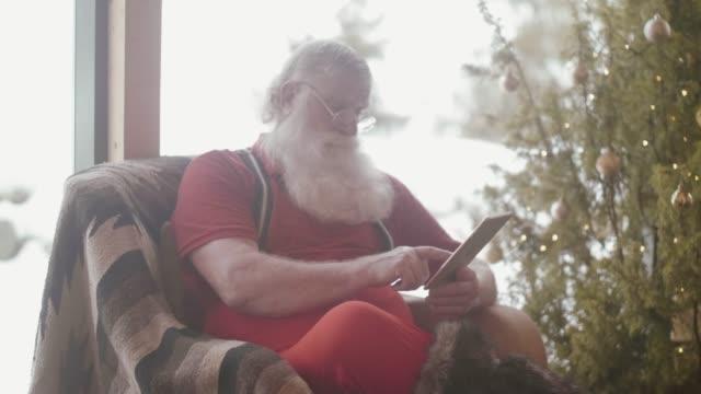 modern santa claus using digital tablet (slow motion) - 2018 video stock e b–roll