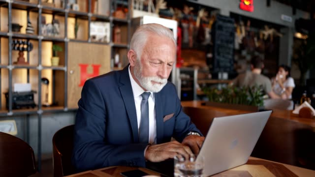 vídeos de stock e filmes b-roll de modern senior businessman working on a work project on a laptop in coffee shop - 50 anos