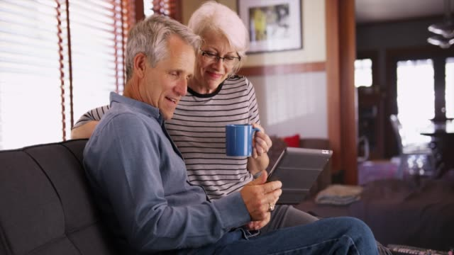 Modern senior couple sitting on couch with tablet