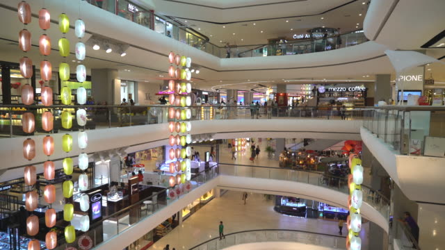 Modern Shopping Mall with stores, Cafe and Shoppers Walking Around