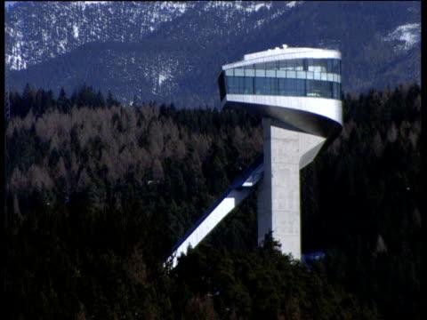 Modern ski jump on mountain beside trees Innsbruck
