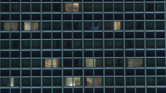 vídeos y material grabado en eventos de stock de modern skyscraper building with illuminated moving windows timelapse - cuadrícula