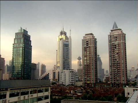 Modern skyscrapers dominating skyline above old slum houses at dusk Shanghai
