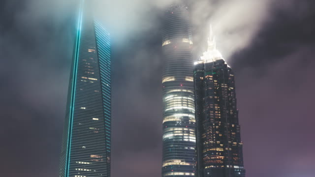 t/l moderne wolkenkratzer in shanghai mit fließendem nebel bei nacht - fensterfront stock-videos und b-roll-filmmaterial