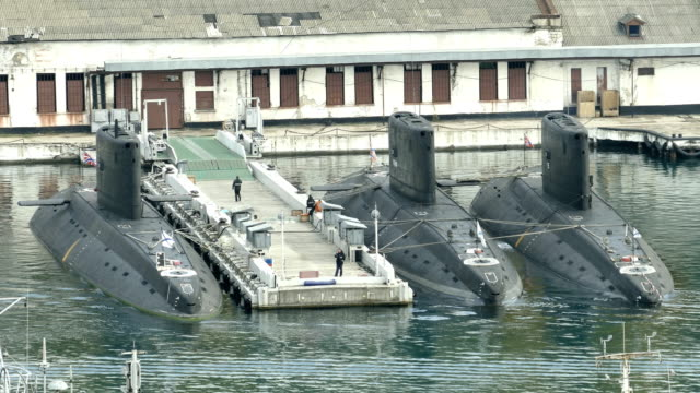 modern submarines at the pier of the military base
