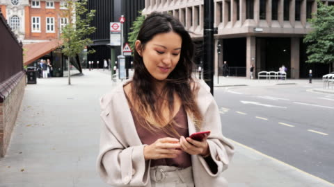 modern taiwanese woman with long hair outdoors using mobile phone - elegance stock videos & royalty-free footage