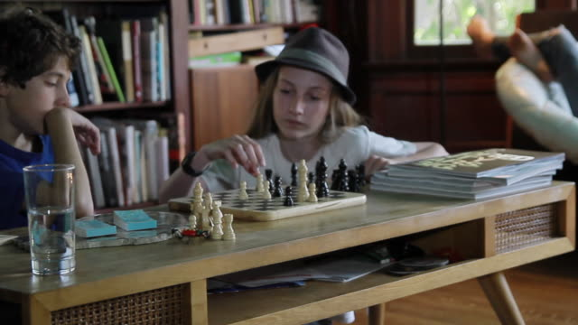 ms pan modern teenagers  playing chess and  listening  music in warm contemporary family room / pasadena, california, united states    - brettspiel stock-videos und b-roll-filmmaterial