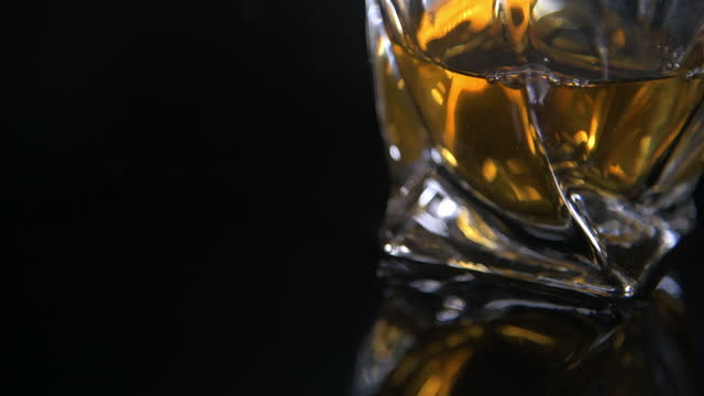 modern tumbler filled with whiskey on black background - fade out video transition stock videos & royalty-free footage