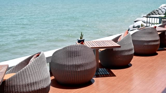 modern weave chairs with wooden table on patio and sea view - patio stock videos & royalty-free footage