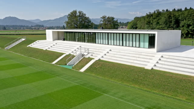 aerial modern white building alongside a football field - football pitch stock videos and b-roll footage