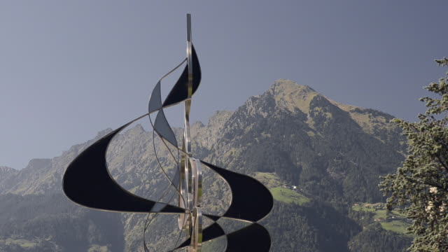 vidéos et rushes de ms modern wind chime turning in wind in front of mountains / merano, tyrol, italy - sculpture production artistique