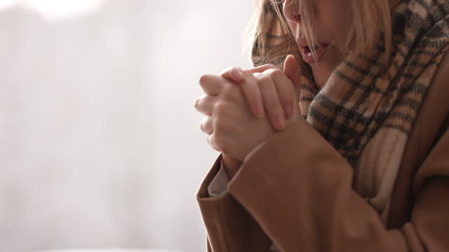 modern woman blowing in her hands so she can stay warm during cold winter day - winter coat stock videos & royalty-free footage