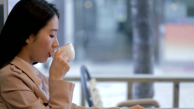 Modern woman drinking coffee alone in cafe