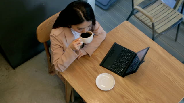 Modern woman drinking coffee alone in cafe with her laptop