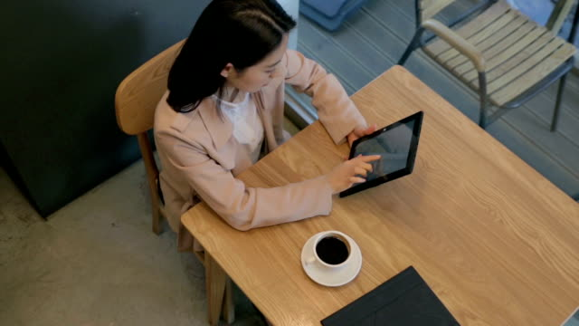 Modern woman drinking coffee alone in cafe with her tablet