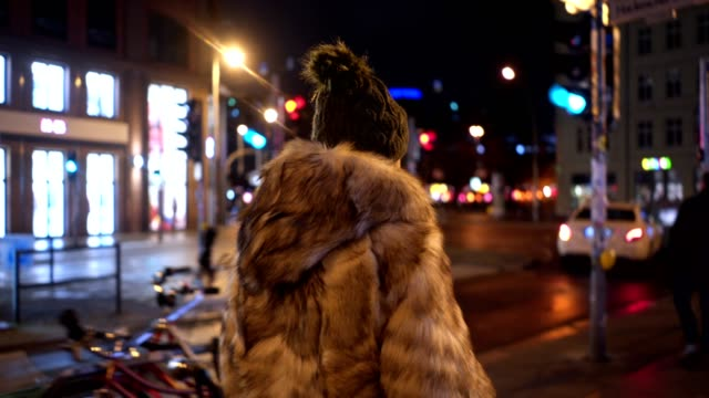 modern woman in a fur coat walking the streets at night - winter coat stock videos & royalty-free footage