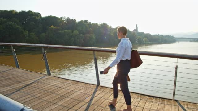 vidéos et rushes de slo mo femme moderne marchant pieds nus à travers un pont - cheveux courts