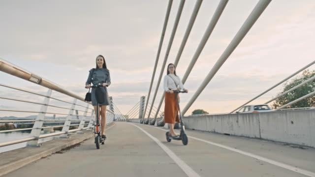 vidéos et rushes de slo mo femmes modernes conduisant des scooters électriques dans la ville - moving past