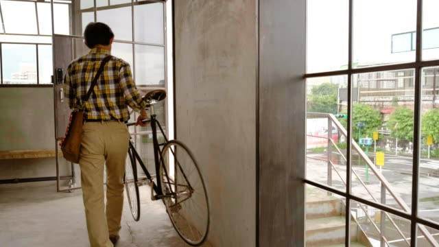 modern worker leaving office with bicycle as a package is delivered - satchel stock videos & royalty-free footage