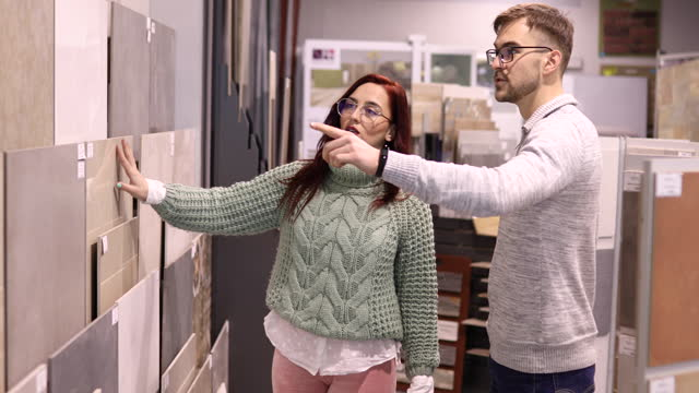 modern young couple at the store showroom, choosing the perfect tile design for their new home - tile stock videos & royalty-free footage
