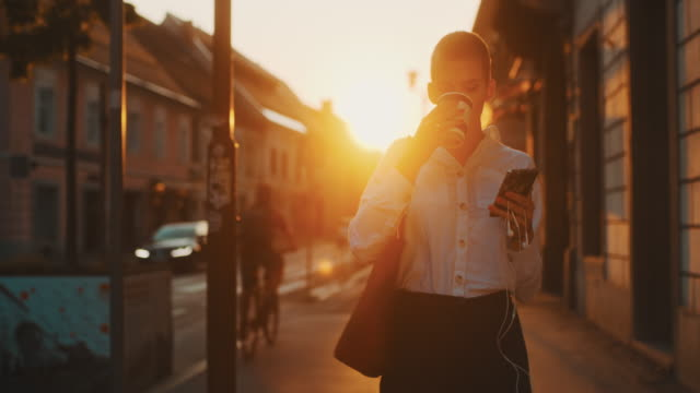 vídeos de stock e filmes b-roll de ms modern young woman walking in the city at sunset, take away coffee - café bebida