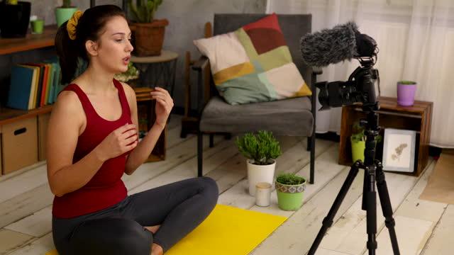 vidéos et rushes de moderne jeune instructeur de yoga enregistrement d'un tutoriel en ligne afin que ses disciples peuvent se détendre pendant ces moments difficiles dans le verrouillage - montrer la voie