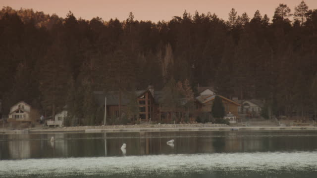 vidéos et rushes de ws modest cabins and a large, rustic home on a quiet lake nestled in the woods - format vignette