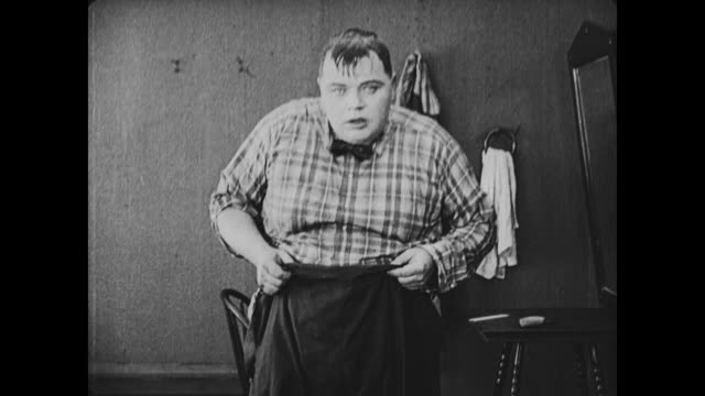 1917 modest man (fatty arbuckle) plays coy as he changes in front of camera in bathhouse - fatty arbuckle stock videos and b-roll footage