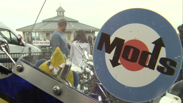 vídeos de stock, filmes e b-roll de mods and rockers descend on margate kent for 50th anniversary of beach clashes shows exterior shots of people walking around vintage scooters 'mods'... - vanguardista