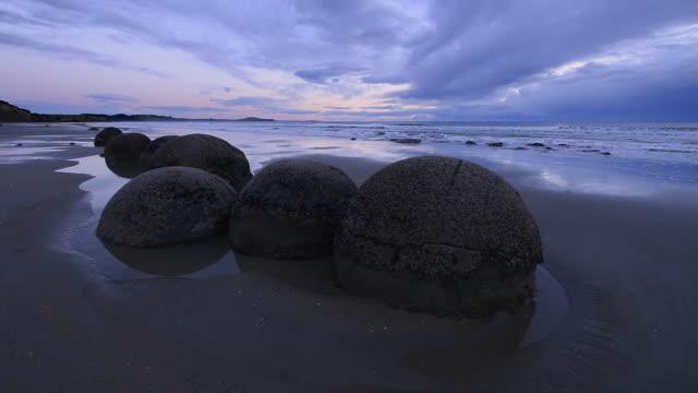 moeraki boulders on koekohe beach with dramatic sky, otago coast, south island of new zealand. moeraki, hampden, koekohe beach, otago coast, south island, new zealand. - geology stock videos & royalty-free footage