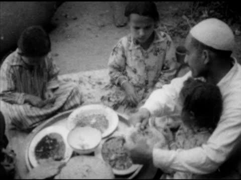 Mohamed Amer family gathered inside for noon main meal VS Eating dipping in bowls w/ flatbread wife Sadia eating children Mohamed eating