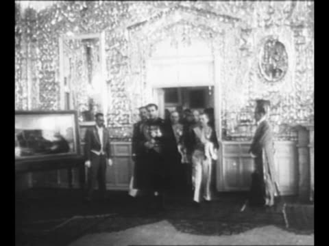 mohammad reza shah pahlavi of iran approaches as he walks past row of cabinet members and military officers inside one of the buildings in the... - military uniform stock videos & royalty-free footage