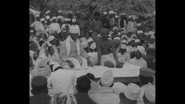 mohandas gandhi sits at an outdoor gathering of his followers at his ashram in india as spokesman speaks / vs gandhi sits on platform under a roof /... - speech stock videos & royalty-free footage