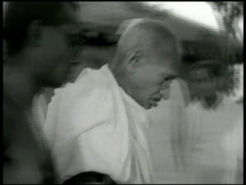 stockvideo's en b-roll-footage met mohatma gandhi walking w/ talking male wiping back of hand w/ cloth while walking. 1949 india: people standing outside exhibition building.... - mahatma gandhi