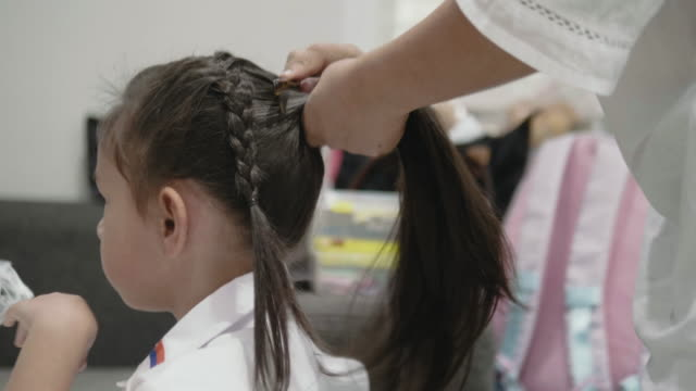 mohter is making hair for her daughter , - ponytail stock videos & royalty-free footage