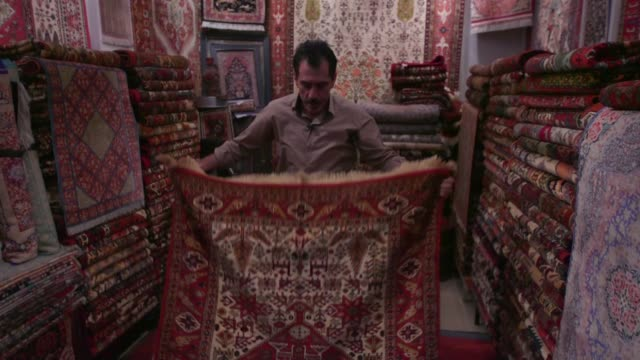 Mojtabah Keshevarz displays and sells Persian rugs in his store Royal Persian Carpets in the Grand Bazaar in Tehran Iran on Sunday Aug 23 2015