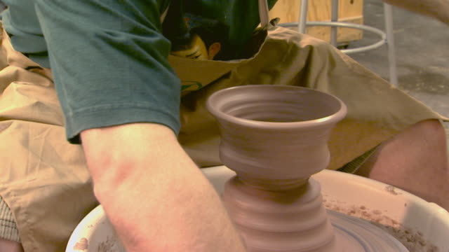 Molding and shaping of clay on a pottery wheel, handheld shot