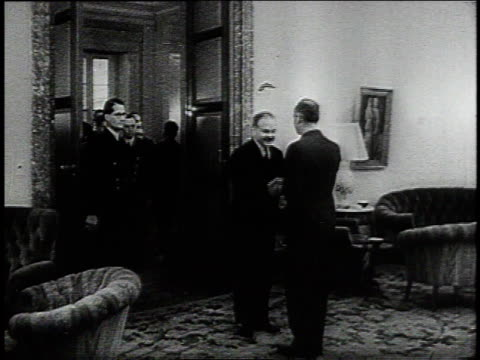 molotov and ribbentrop entering room and shaking hands / sitting down at a table with diplomats milling behind them - vyacheslav m. molotov stock videos and b-roll footage