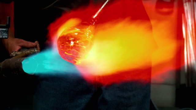 CU ZO ZI Molten glass piece being rolled and torched by artist glassblower, Santa Barbara, California, USA