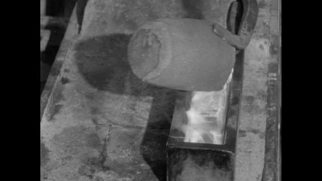 molten gold from crucible poured into mould; 1956 - 1956 stock-videos und b-roll-filmmaterial