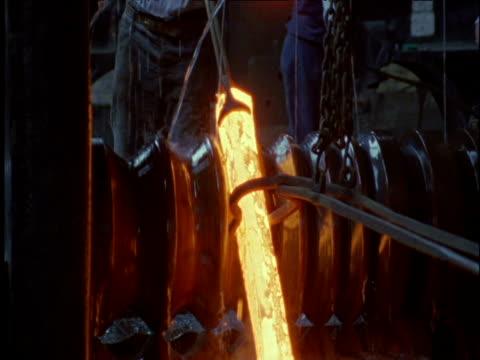 vídeos de stock e filmes b-roll de molten iron bar being run through rollers in forge ironbridge - ferro metal