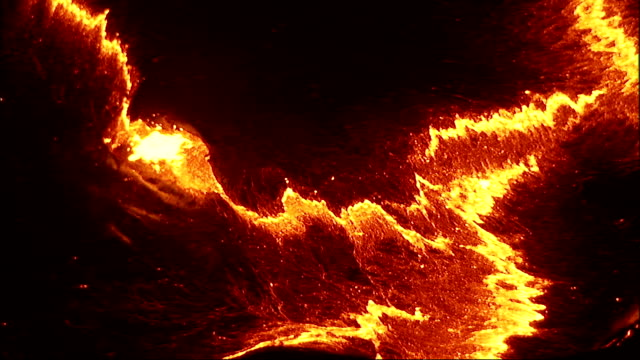 Molten lava bubbles and splashes at a volcano's surface. Available in HD.