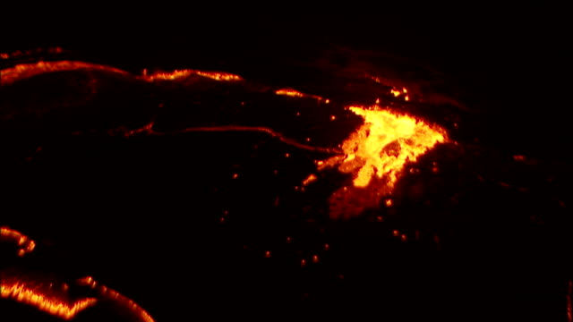 Molten lava bubbles and spurts through surface crust in volcano crater. Available in HD.