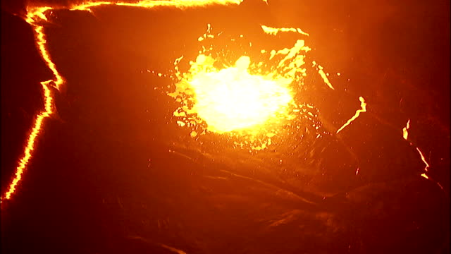 Molten lava bursts through surface crust in volcano crater. Available in HD.