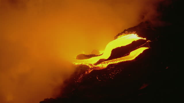 Molten lava flow with large steam cloud in Hawaii Volcanoes National Park at night.